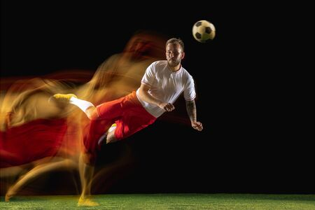 In second. Young caucasian male football or soccer player in sportwear and boots kicking ball for the goal in mixed light on dark background. Concept of healthy lifestyle, professional sport, hobby.