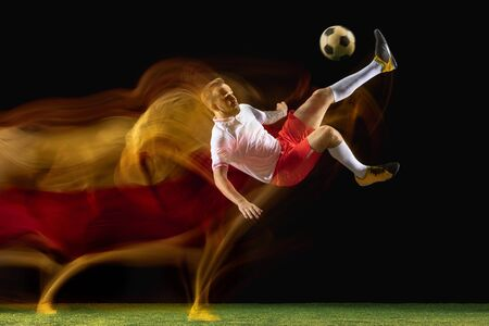 Overcome. Young caucasian male football or soccer player in sportwear and boots kicking ball for the goal in mixed light on dark background. Concept of healthy lifestyle, professional sport, hobby.