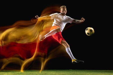 Confident. Young caucasian male football or soccer player in sportwear and boots kicking ball for the goal in mixed light on dark background. Concept of healthy lifestyle, professional sport, hobby.