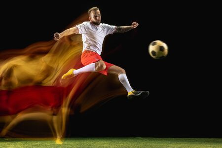 To win. Young caucasian male football or soccer player in sportwear and boots kicking ball for the goal in mixed light on dark background. Concept of healthy lifestyle, professional sport, hobby.