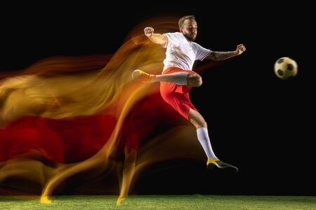 Concentrated. Young caucasian male football or soccer player in sportwear and boots kicking ball for the goal in mixed light on dark background. Concept of healthy lifestyle, professional sport, hobby. Imagens