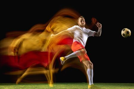 Chooses win. Young caucasian male football or soccer player in sportwear and boots kicking ball for the goal in mixed light on dark background. Concept of healthy lifestyle, professional sport, hobby. Imagens