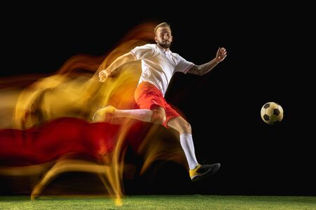 Strong. Young caucasian male football or soccer player in sportwear and boots kicking ball for the goal in mixed light on dark background. Concept of healthy lifestyle, professional sport, hobby.