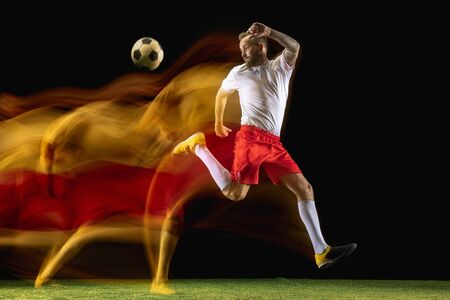 Fighter. Young caucasian male football or soccer player in sportwear and boots kicking ball for the goal in mixed light on dark background. Concept of healthy lifestyle, professional sport, hobby.
