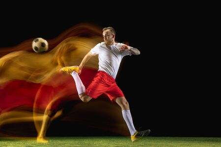 Young caucasian male football or soccer player in sportwear and boots kicking ball for the goal in mixed light on dark background. Concept of healthy lifestyle, professional sport, hobby.