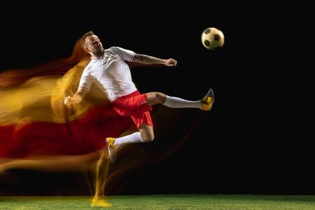 Catch up. Young caucasian male football or soccer player in sportwear and boots kicking ball for the goal in mixed light on dark background. Concept of healthy lifestyle, professional sport, hobby.