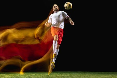 Champion. Young caucasian male football or soccer player in sportwear and boots kicking ball for the goal in mixed light on dark background. Concept of healthy lifestyle, professional sport, hobby.