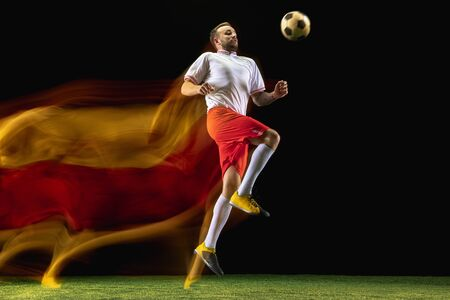 Expression. Young caucasian male football or soccer player in sportwear and boots kicking ball for the goal in mixed light on dark background. Concept of healthy lifestyle, professional sport, hobby.