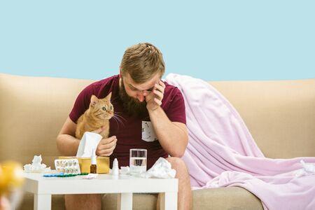 Junger Mann, der an einer Katzenhaarallergie leidet. Hautausschlag, Juckreiz, Niesen in die Serviette, Sitzen, umgeben von gebrauchten Servietten, Halten des Tieres. Einnahme von Medikamenten ohne Ergebnis. Gesundheitskonzept. Standard-Bild