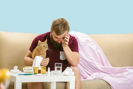 Young man suffering from allergy to cat hair. Having skin rash, itching, Sneezing in the napkin, sitting surrounded by used napkins, holding the pet. Taking medicine with no result. Healthcare concept. Фото со стока - 128383719