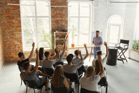 Orador masculino dando presentación en el salón del taller universitario. Audiencia o sala de conferencias. Vista trasera de participantes no reconocidos en audiencia. Evento de conferencia científica, formación. Concepto de educación.