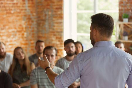 Orateur masculin faisant une présentation dans le hall de l'atelier universitaire. Salle d'audience ou de conférence. Les élèves posent une question, l'enseignant donne une réponse. Conférence scientifique événement, formation. Éducation.
