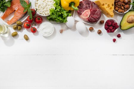 Ketogenic low carbs diet - food selection on white background. Balanced healthy organic ingredients of high content of fats for the heart and blood vessels. Meat, fish and vegetables. Copyspace. 写真素材