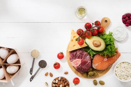 Ketogenic low carbs diet - food selection on white background. Balanced healthy organic ingredients of high content of fats for the heart and blood vessels. Meat, fish and vegetables. Copyspace. Stock Photo