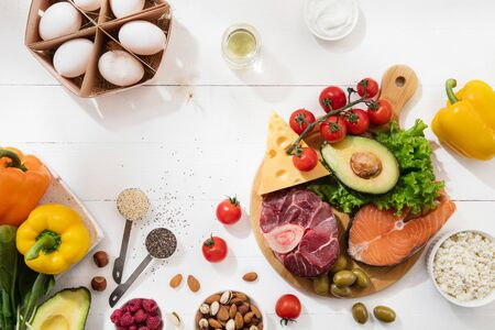Ketogenic low carbs diet - food selection on white wooden background. Balanced healthy organic ingredients of high content of fats. Nutrition for the heart and blood vessels. Meat, fish and vegetables.