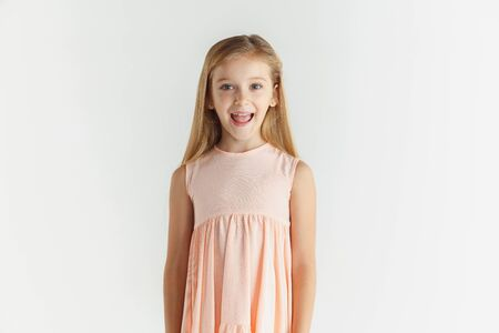 Stylish little smiling girl posing in dress isolated on white studio background. Caucasian blonde female model. Human emotions, facial expression, childhood. Wondered, looking at camera.