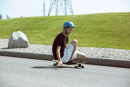 Skateboarder doing a trick at the citys street in sunny day. Young man in equipment riding and longboarding on the asphalt in action. Concept of leisure activity, sport, extreme, hobby and motion.
