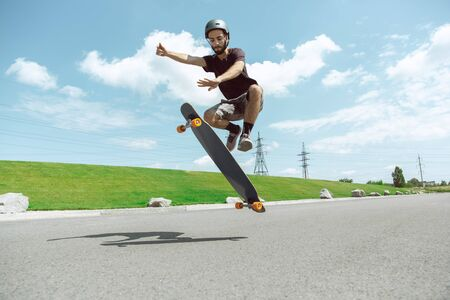 Skateboarder doing a trick at the citys street in sunny day. Young man in equipment riding and longboarding near by meadow in action. Concept of leisure activity, sport, extreme, hobby and motion. Banque d'images