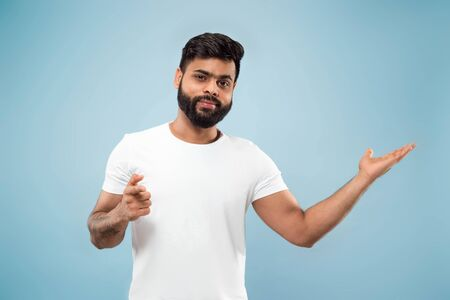 Half-length close up portrait of young hindoo man in white shirt on blue background. Human emotions, facial expression, ad concept. Negative space. Showing empty bar, pointing, choosing, inviting.