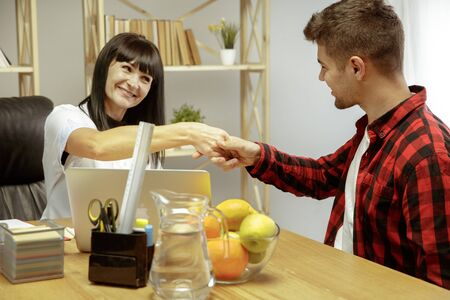 Smiling nutritionist showing a healthy diet plan to patient. Young man visiting a doctor for having a nutrition recommendations. Concept of healthy lifestyle and food, medicine and treatment. Stock Photo