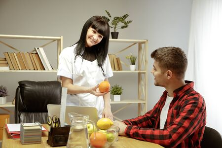 Smiling nutritionist showing a healthy diet plan to patient. Young man visiting a doctor for having a nutrition recommendations. Concept of healthy lifestyle and food, medicine and treatment.