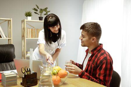 Nutritionniste souriante montrant un régime alimentaire sain au patient. Jeune homme visitant un médecin pour avoir des recommandations nutritionnelles. Concept de mode de vie sain et d'alimentation, de médecine et de traitement.