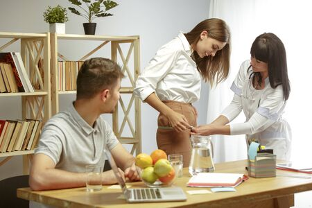 Smiling nutritionist diagnoses physique of patient. Young couple visiting a doctor for having a nutrition recommendations and diet plan. Healthy lifestyle and food, medicine and treatment.