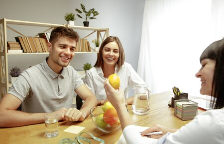 Smiling nutritionist showing a healthy diet plan and fruits to patient. Young couple visiting a doctor for having a nutrition recommendations. Healthy lifestyle and food, medicine and treatment.