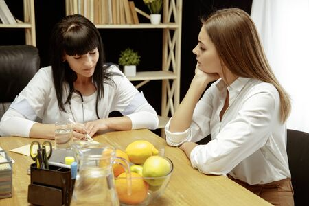 Smiling nutritionist showing a healthy diet plan to patient. Young woman visiting a doctor for having a nutrition recommendations. Concept of healthy lifestyle and food, medicine and treatment. Stock Photo