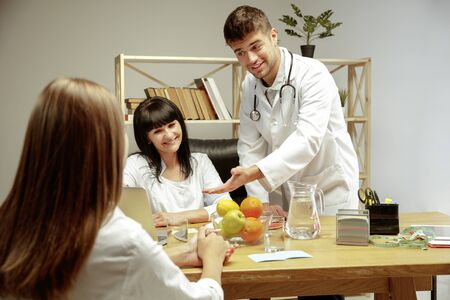 Smiling nutritionists showing a healthy diet plan to patient. Young woman visiting a doctor for having a nutrition recommendations. Concept of healthy lifestyle and food, medicine and treatment.
