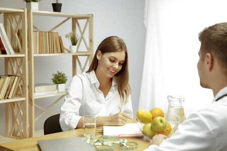 Young womans visiting a doctor for having a nutrition recommendations. Male nutritionist make a healthy diet plan up to patient. Concept of healthy lifestyle and food, medicine and treatment.