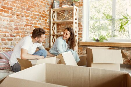 Young couple moved to a new house or apartment. Unpacking cardboard boxes together, having fun at moved day. Look happy, dreamful and confident. Family, moving, relations, first home concept. Archivio Fotografico