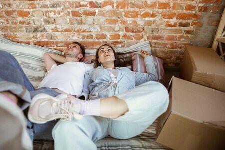 Junges Paar zog in ein neues Haus oder eine neue Wohnung. Zusammen liegen, entspannen nach dem Putzen und Auspacken am bewegten Tag. Sehen Sie glücklich, verträumt und selbstbewusst aus. Familie, Umzug, Beziehungen, erstes Wohnkonzept. Standard-Bild
