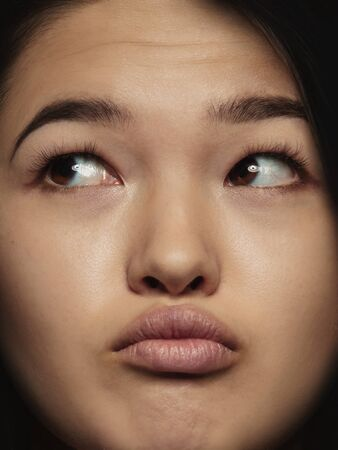 Close up portrait of young and emotional chinese woman. Highly detail photoshot of female model with well-kept skin and bright facial expression. Concept of human emotions. Thinking, looking at side. Stock Photo