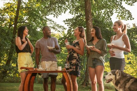 Group of happy friends eating and drinking beers at barbecue dinner on sunset time. Having meal together outdoor in a forest glade. Celebrating and relaxing. Summer lifestyle, food, friendship concept.