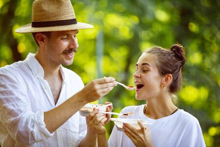 Happy couple eating at barbecue dinner on sunset time. Having meal together outdoor in a forest glade. Look happy together. Celebrating and relaxing. Summer lifestyle, food, family, relation concept. Banco de Imagens