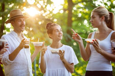 Group of happy friends eating at barbecue dinner on sunset time. Having meal together outdoor in a forest glade. Celebrating and relaxing, laughting. Summer lifestyle, food, friendship concept.