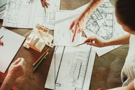 Top view of achitect-engineers hands shows future house, office or store design plans to a young couple. Meeting at the construction office to talk about facade, interior decoration, home layout. Zdjęcie Seryjne