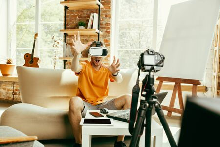 Young caucasian male blogger with professional equipment recording video review of VR glasses at home. Blogging, videoblog, vlogging. Man using virtual reality headset while streaming live.