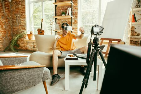 Full of emotions. Caucasian male blogger with professional camera recording video review of VR glasses at home. Blogging, videoblog, vlogging. Man using virtual reality headset while streaming live. Banco de Imagens
