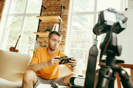 Young caucasian male blogger with professional equipment recording video review of VR glasses at home. Blogging, videoblog, vlogging. Man evaluates virtual reality headset while streaming live.