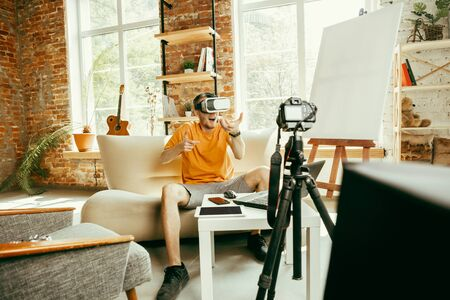 Full of emotions. Caucasian male blogger with professional camera recording video review of VR glasses at home. Blogging, videoblog, vlogging. Man using virtual reality headset while streaming live. Stockfoto