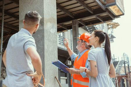 Foreman or achitect engineer shows future house, office or store design plans to a young couple. Meeting at the construction site to talk about facade appearance, interior decoration, home layout.