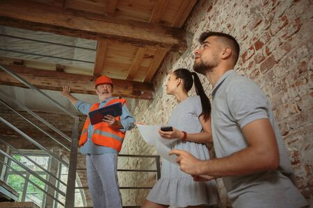 Foreman or achitect engineer shows future house, office or store design plans to a young couple. Meeting at the construction site to talk about interior, communications, home layout, placement of rooms.