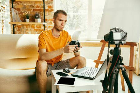 Young caucasian male blogger with professional equipment recording video review of camera at home. Blogging, videoblog, vlogging. Man making vlog or live stream about photo or technical novelty.