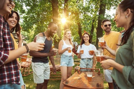 Group of happy friends having beer and barbecue party at sunny day. Resting together outdoor in a forest glade or backyard. Celebrating and relaxing, laughting. Summer lifestyle, friendship concept. Stockfoto - 128551710