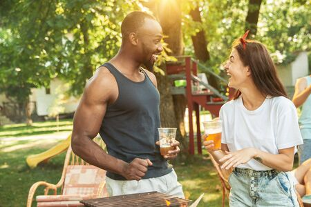 Group of happy friends having beer and barbecue party at sunny day. Resting together outdoor in a forest glade or backyard. Celebrating and relaxing, laughting. Summer lifestyle, friendship concept. Stockfoto - 128551708