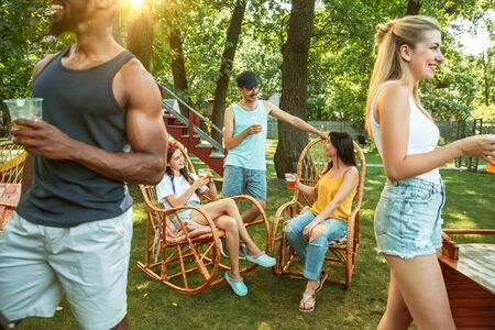 Group of happy friends having beer and barbecue party at sunny day. Resting together outdoor in a forest glade or backyard. Celebrating and relaxing, laughting. Summer lifestyle, friendship concept. Stockfoto - 128551718