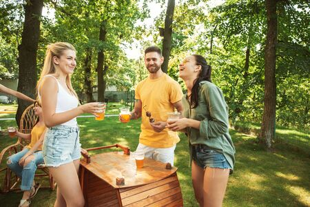 Group of happy friends having beer and barbecue party at sunny day. Resting together outdoor in a forest glade or backyard. Celebrating and relaxing, laughting. Summer lifestyle, friendship concept. Stockfoto - 128551732