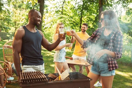 Group of happy friends having beer and barbecue party at sunny day. Resting together outdoor in a forest glade or backyard. Celebrating and relaxing, laughting. Summer lifestyle, friendship concept. Stockfoto - 128551728